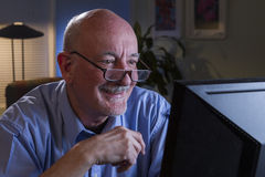 Close up of serious older man using home computer, horizontal Royalty Free Stock Images