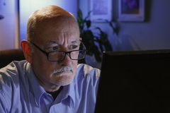 Close up of serious older man using home computer, horizontal Stock Photography