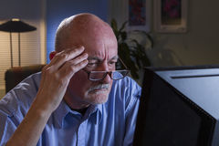 Close up of serious older man using home computer, horizontal Royalty Free Stock Photos