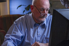 Close up of serious older man using home computer, horizontal Stock Photo