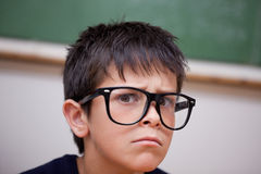 Close up of a serious schoolboy. In a classroom Stock Image