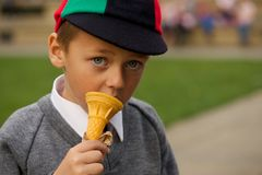 Close-up of serious uniformed schoolboy eating ice-cream Royalty Free Stock Image