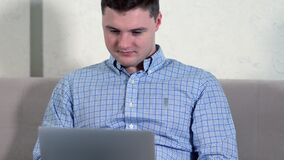 Close up on a serious young man using a laptop