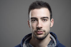 Close up of serious young unshaven man wearing hoodie. Looking at camera Stock Photo