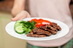 Close-up serving homemade grilled beef medallions with grilled pepper, fresh cucumber and parsley on a round white plate. Concept stock image