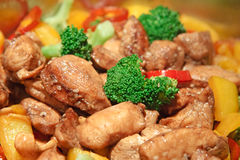 Close up of sesame chicken stir-fry. Golden chicken with sesame seeds, cashew nuts, red and yellow bell peppers and broccoli Royalty Free Stock Photos