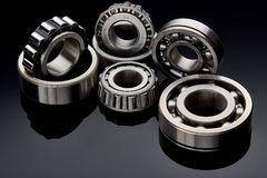 Close-up of a set of ball and roller bearings on a dark background. Close-up of a set of ball and roller bearings for repair lying on the desktop in the dark royalty free stock image
