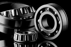 Close-up of a set of ball and roller bearings on a dark background. Close-up of a set of ball and roller bearings for repair lying on the desktop in the dark royalty free stock photo