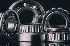 Close-up of a set of ball and roller bearings on a dark background. Close-up of a set of ball and roller bearings for repair lying on the desktop in the dark royalty free stock photos