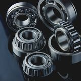 Close-up of a set of ball and roller bearings on a dark background. Close-up of a set of ball and roller bearings for repair lying on the desktop in the dark stock image