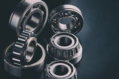 Close-up of a set of ball and roller bearings on a dark background. Close-up of a set of ball and roller bearings for repair lying on the desktop in the dark stock photos