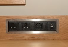 Set of power sockets. A close up of a set of black power sockets on a wooden board Stock Image