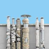 Set of old ventilation chimneys against blue sky stock image