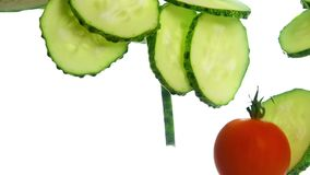 Cucumber and cherry tomatoes floating in water. Close up several fresh green cucumber slices and red cherry tomatoes thrown and floating in clear transparent stock video footage