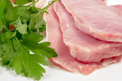 Close-up of several raw pork loins with fresh parsley Stock Images