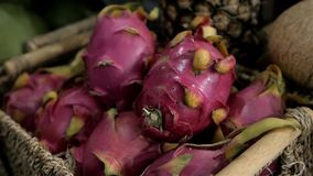 Close up several red ripe pitaya or white pitahaya dragon fruit with one cut cross section half on market stall, high. Angle view stock video footage