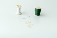 Close up of sewing items,Spool of thread, needle and button. Isolated on white background stock image