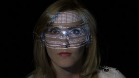 Blonde hacker girl reading programming code in virtual reality space while the data characters are projected on her face -. Close up of a blonde hacker girl stock footage