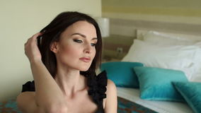 Close-up of sexy girl sitting on the bed in hotel. Gorgeous sexy girl in a black dress is sitting on the bed, in the background are the blue pillows. Close-up stock video