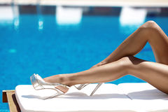 Close up sexy tanned long legs in high heels lying on deck chair. Against the swimming pool with blue water Stock Photos