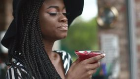 Close-up of and thoughtful african american lady in black hat and striped vogue dress with cool cocktail in bar stock footage