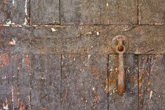 Close-up of shabby wooden door with rusty doorbell Stock Image
