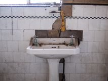 Close up of Shanks hand basin and original tiles in derelict deco style house. House is due for demolition. Harrow UK stock photography