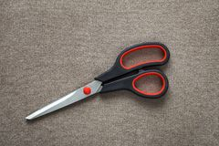 Close-up of sharp steel metal scissors isolated on light cloth copy space background. Household equipment, office or school tools.  royalty free stock photo