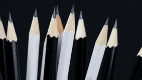 Sharpened tip of black and white pencils on black background stock photography