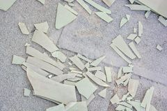 Pieces of broken plastic sheet on ground. Close up shattered light green plastic sheet on ground royalty free stock photography