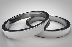 Close Up of 2 Shinny Silver Rings on grey background. Close Up of 2 elegant silver rings on grey gradient. Great for covers, magazines, posters, backdrops etc Stock Photography