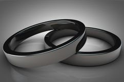 Close Up of 2 Shinny Silver Rings on grey background. Close Up of 2 elegant silver rings on grey gradient. Great for covers, magazines, posters, backdrops etc Royalty Free Stock Photos