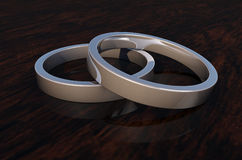 Close Up of 2 Shinny Silver Rings on Woodenbase. CloseUp 2 elegant silver rings on wooden base. Great for covers, magazines, posters, backdrops etc Stock Photography