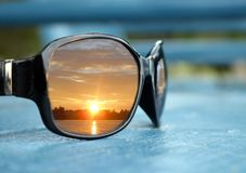Closeup of shiny black sunglasses with sunset reflection in lens on blue chair stock photography