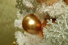 Close-up of a shiny pink-gold ball shaped Christmas ornament with blurred silver glitter snowflake ornaments Royalty Free Stock Photos