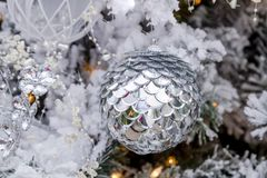 Christmas ornaments hanging on tree. Close up of shiny silver Christmas ornament hanging on frosted white Christmas tree with lights and jewels Royalty Free Stock Image