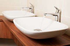 Close-up of shiny taps with flowing water and ceramic sinks. In a public washroom royalty free stock photos