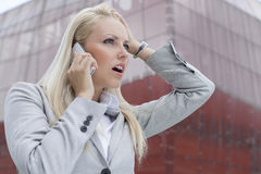 Close-up of shocked businesswoman communicating on cell phone against office building Royalty Free Stock Photography