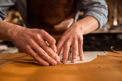 Close up of a shoemaker cutting leather. In a workshop royalty free stock photos