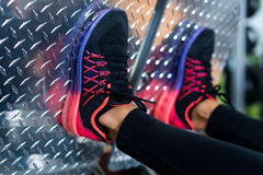 Close up shoes of a fit young woman doing leg press in the gym Stock Photo