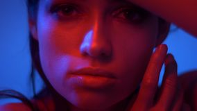 Close-up shoot of fashion model in red and blue neon lights hiding her face with fingers and watches into camera. Close-up shoot of fashion model in red and stock footage