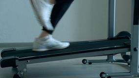 Female foots running on treadmill at home. Close up shoot - female foots running on treadmill at home stock video footage