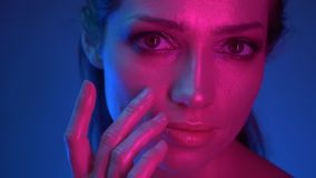 Close-up shoot of model with glitter makeup in blue and pink neon lights covers her face with fingers watching into. Camera keenly stock footage