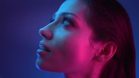 Close-up shoot in profile of model in blue and pink neon lights watching upwards with amusement and reaching out to stock video