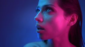Close-up shoot in profile of model with glitter makeup in blue and pink neon lights watching upwards with strong stock footage