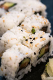 A close-up shoot of Uramaki sushi rolls with fresh salmon, avocado and philadelphia cheese, covered with sesame seeds Stock Photo