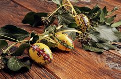 Close up shoot of yellow hand painted easter eggs decorated with green ivy branches on a vintage, wooden table royalty free stock photos