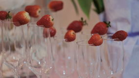 Close up shooting glasses for alcoholic on party outdoors. Table with white tablecloth bar with glass for champagne with strawberry on edge delicious stock video footage