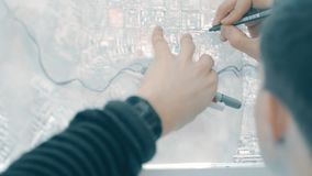 Close up shooting hands manager man, standing working with map. Close to window in office hall. male look at design drawings for construction of large sports stock footage