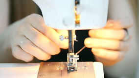 Close-up shooting hands putting pink thread in sewing machine stock video